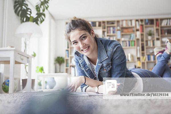Porträt einer lächelnden jungen Frau  die sich zu Hause entspannt