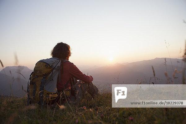Österreich  Tirol  Unterberghorn  Wanderer in alpiner Landschaft bei Sonnenuntergang