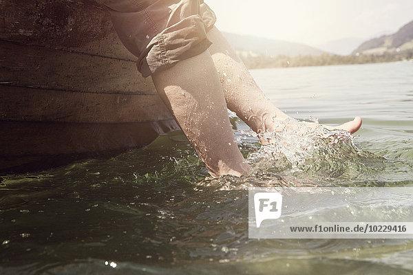 Österreich  Tirol  Frauenfüße planschen im Wasser des Walchsees