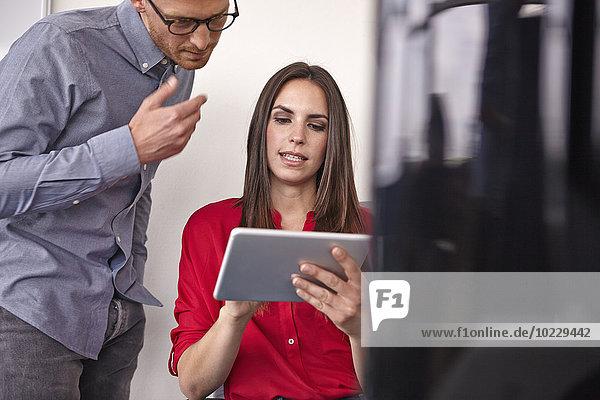 Mann und Frau im Büro suchen auf digitalem Tablett