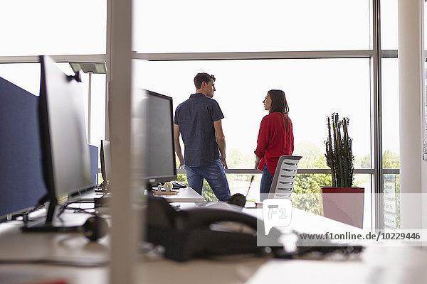 Zwei Kollegen im Großraumbüro im Gespräch am Fenster