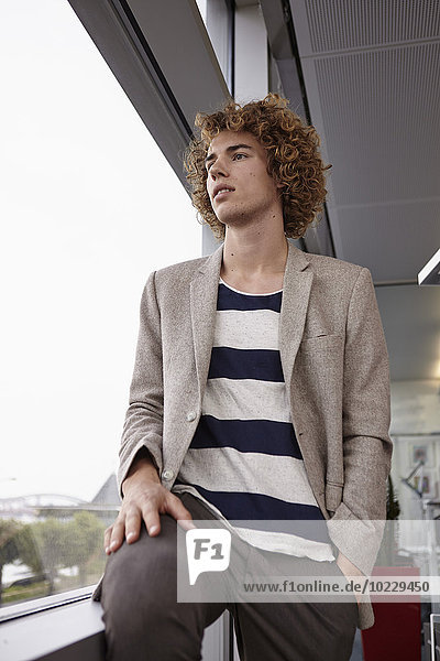 Young man with curly hair looking out of window