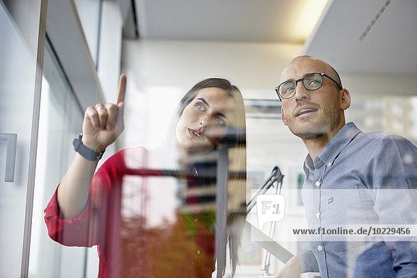 Mann und Frau im Büro diskutieren hinter der Glasscheibe