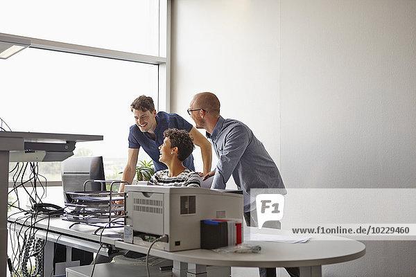 Drei lächelnde Kollegen am Schreibtisch