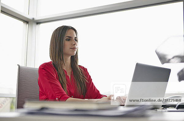 Junge Frau mit Laptop im Büro