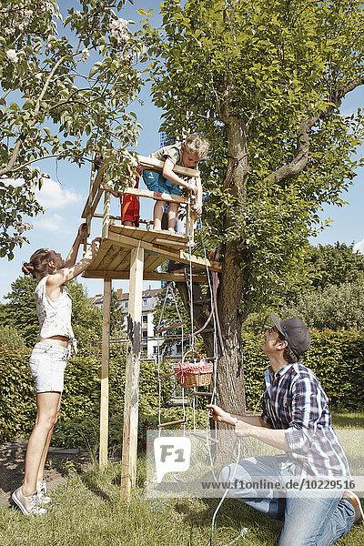 Familienspiel im Baumhaus im Garten