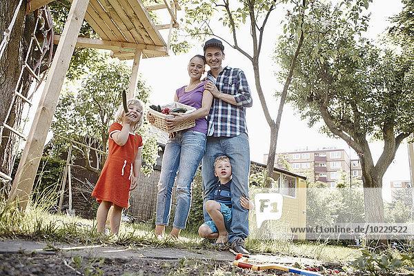 Fröhlicher Familienkorb mit frischem Gemüse im Garten