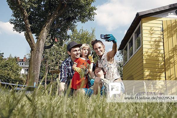 Glückliche Familie im Garten mit einem Selfie