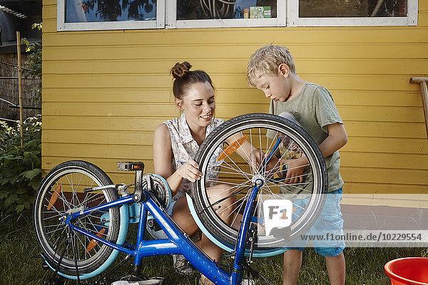 Mutter und Sohn reparieren gemeinsam das Fahrrad