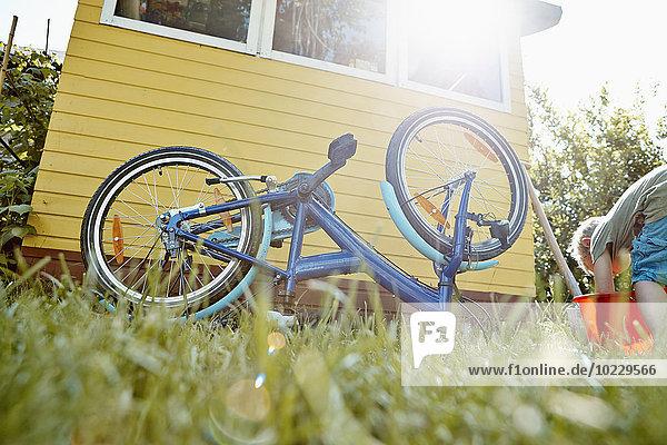 Junge repariert Fahrrad im Garten