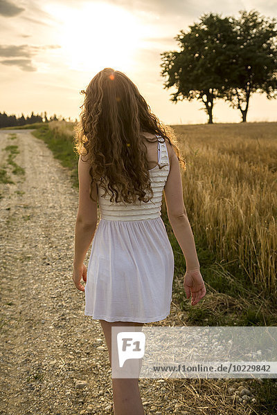 Junge Frau auf Feldweg  Abendsonne
