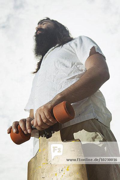 Flachwinkelansicht eines Mannes vom Typ Hipster mit Longboard