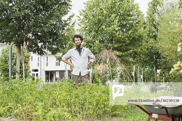 Junger Mann steht in einem städtischen Garten