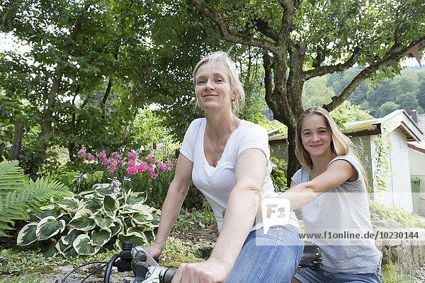 Mutter und Tochter fahren auf einem Fahrrad