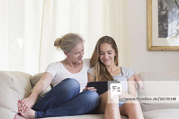 Mutter und Tochter sitzend mit digitalem Tablett auf der Couch