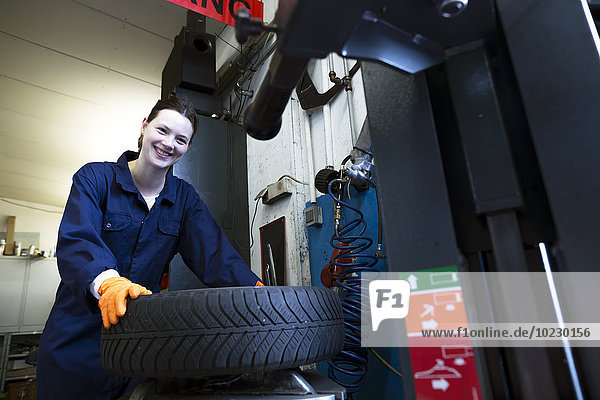 Young woman working in repair garage taking car tire