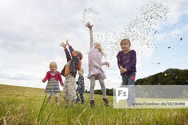Fünf kleine Kinder  die Konfetti auf eine Wiese werfen.