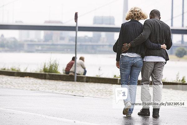 Junges Paar beim Spaziergang am Flussufer