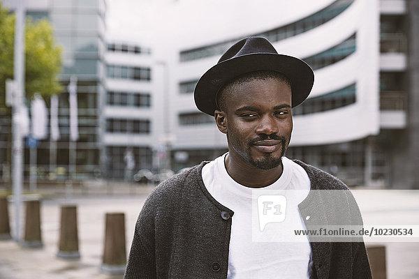 Porträt eines lächelnden jungen Mannes mit Hut im Freien