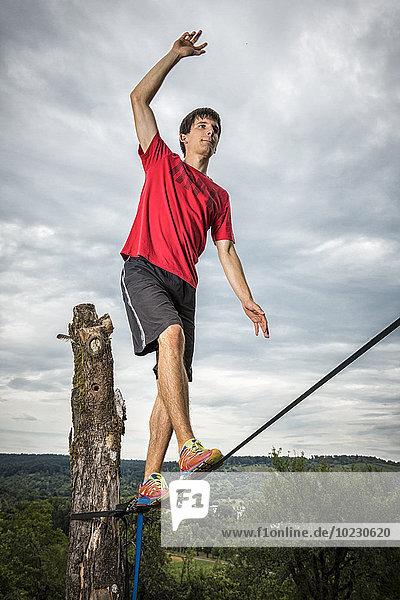 Junger Mann balanciert auf der Slackline