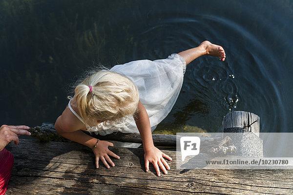 Mädchen im Sommerkleid mit Fuß im See