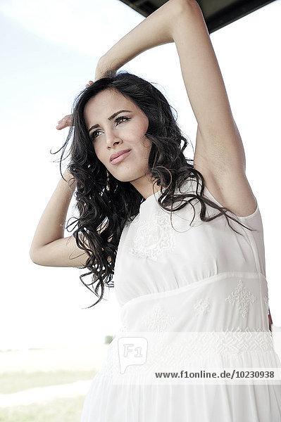Porträt einer dunkelhaarigen jungen Frau in weißem Kleid
