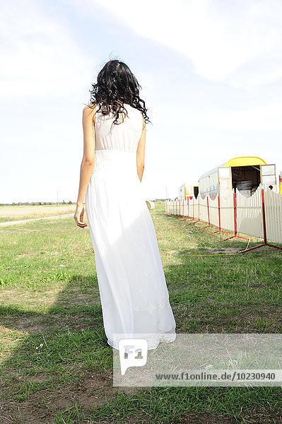 Dunkelhaarige junge Frau in weißem Kleid auf einer Wiese stehend