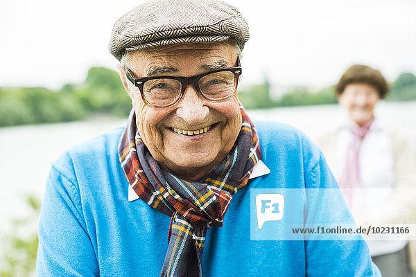 Porträt eines glücklichen älteren Mannes mit Brille und Kappe