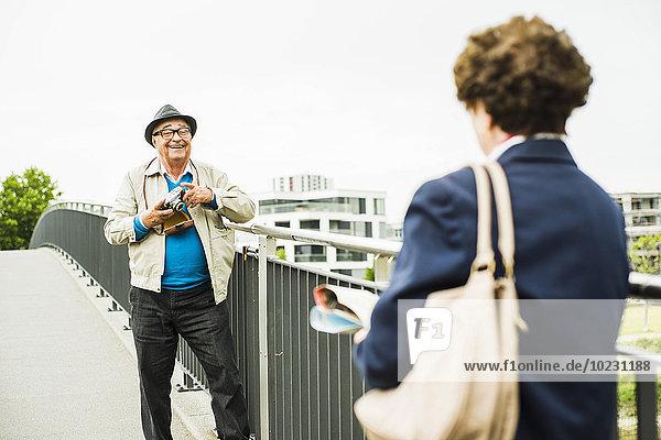 Ein älterer Mann macht ein Foto von seiner Frau.