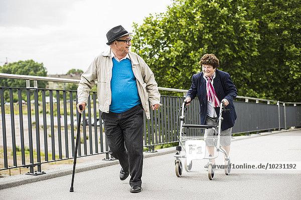 Seniorenpaar mit Gehstock und Rollator