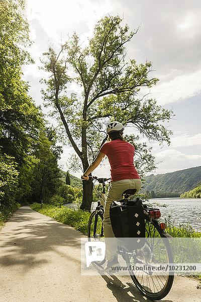 Deutschland  Cochem  Frau auf dem Fahrrad entlang der Mosel