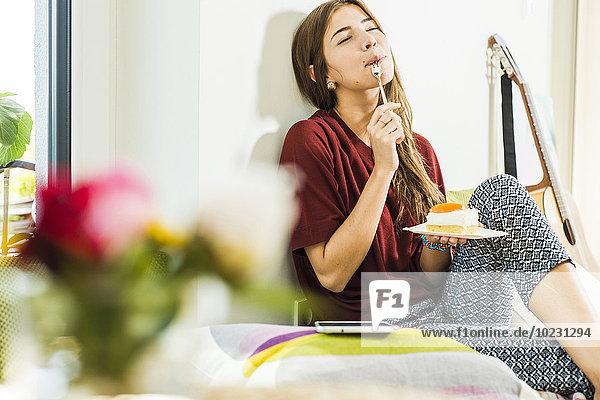 Junge Frau zu Hause mit einem Stück Kuchen im Bett