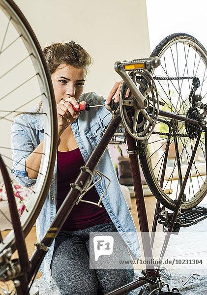 Junge Frau zu Hause repariert ihr Fahrrad