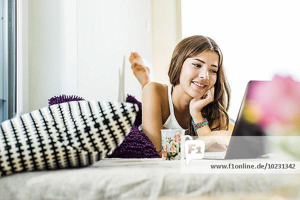 Entspannte junge Frau im Bett liegend mit Laptop