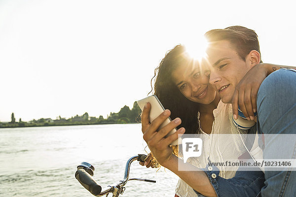 Junges Paar mit Fahrrad und Handy am Flussufer
