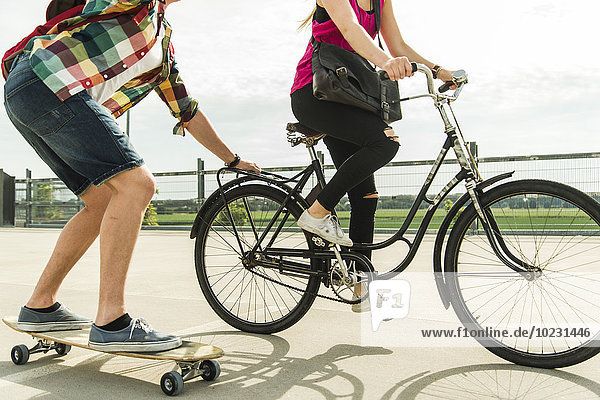 Junges Paar beim Radfahren und Skateboardfahren