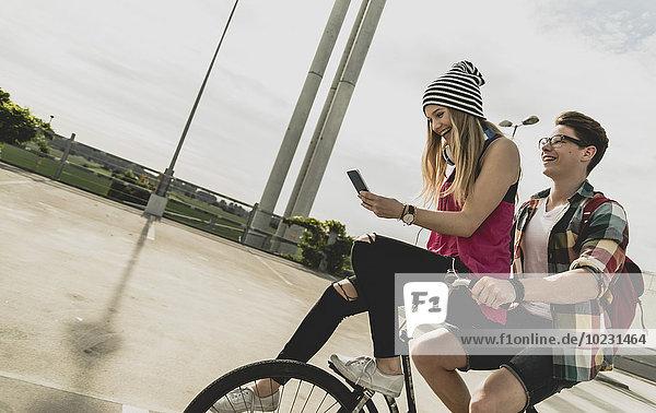 Glückliches junges Paar mit Handy zusammen auf dem Fahrrad