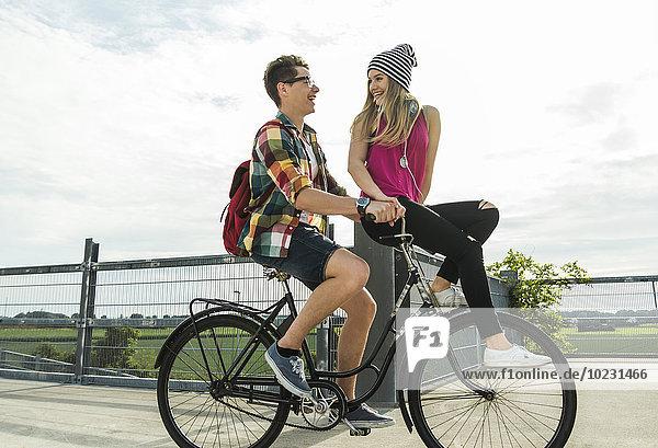 Glückliches junges Paar zusammen auf dem Fahrrad