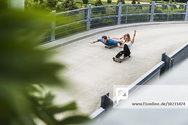 Begeistertes junges Paar beim Abfahren mit Skateboards