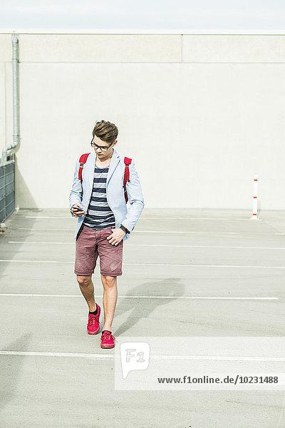 Junger Mann  der auf dem Handy nach draußen geht.