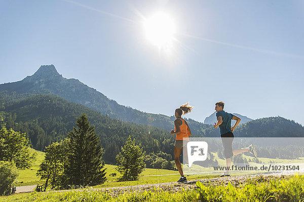Österreich  Tirol  Tannheimer Tal  junges Paar Joggen in alpiner Landschaft