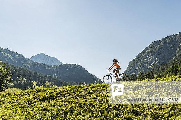 Austria  Tyrol  Tannheim Valley  young woman on mountain bike in alpine landscape