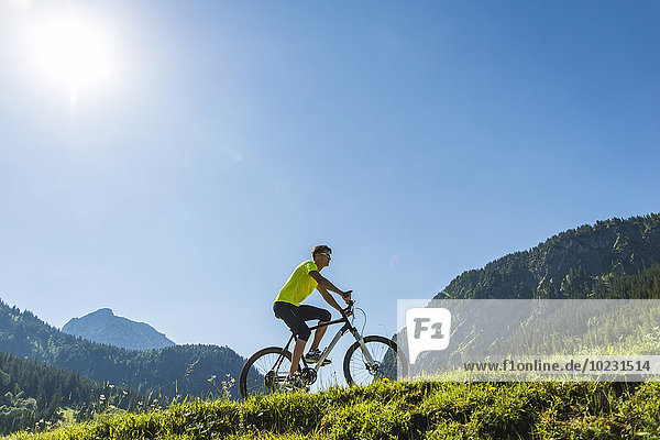 Austria  Tyrol  Tannheim Valley  young man on mountain bike in alpine landscape