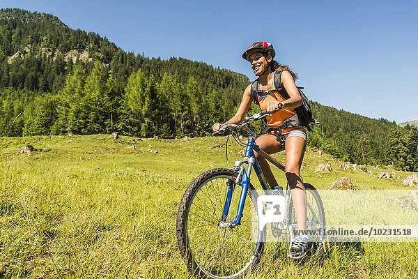 Österreich  Tirol  Tannheimer Tal  glückliche junge Frau auf dem Mountainbike in alpiner Landschaft