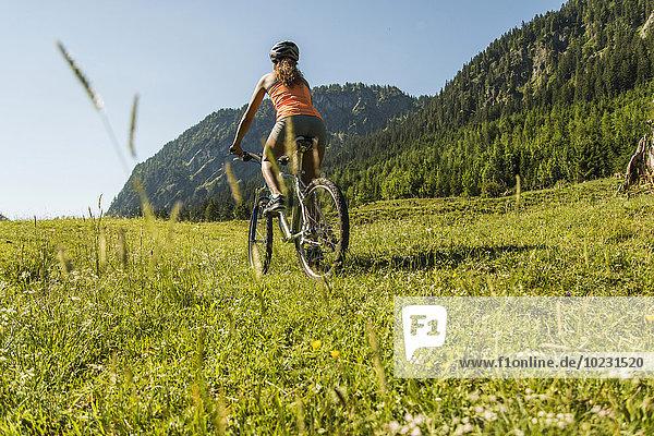 Österreich  Tirol  Tannheimer Tal  junge Frau auf dem Mountainbike in alpiner Landschaft