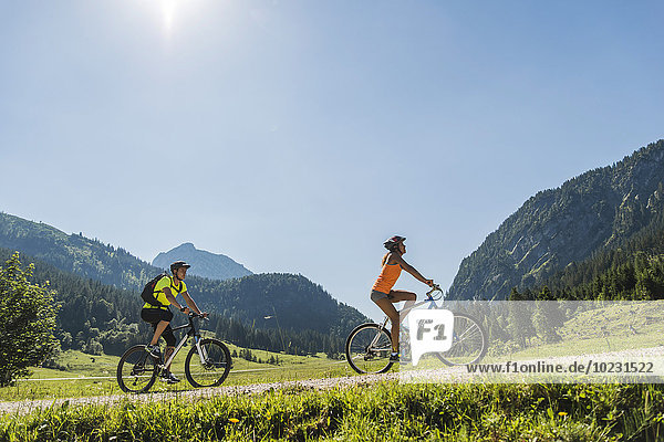 Austria  Tyrol  Tannheim Valley  young couple on mountain bikes in alpine landscape