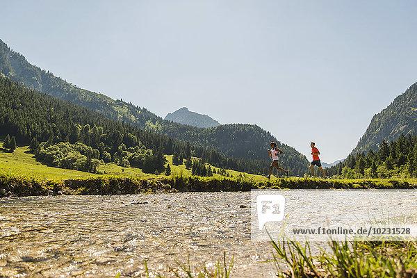 Österreich  Tirol  Tannheimer Tal  junges Paar joggen am Flussufer