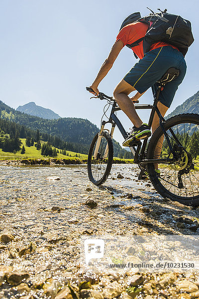 Österreich  Tirol  Tannheimer Tal  junger Mann auf dem Mountainbike überquert Bach