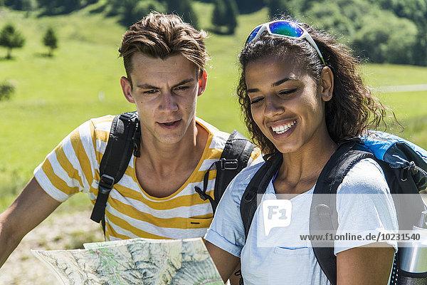 Österreich  Tirol  Tannheimer Tal  junges Paar auf der Landkarte