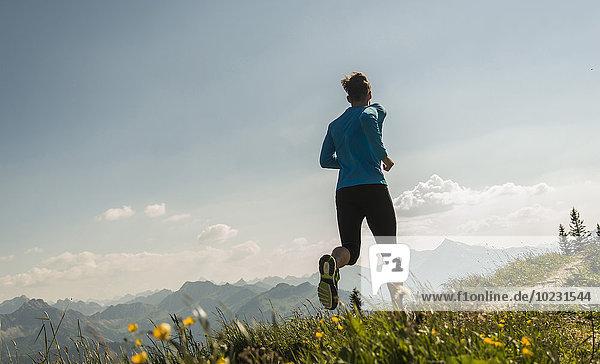 Österreich  Tirol  Tannheimer Tal  junger Mann beim Joggen in den Bergen